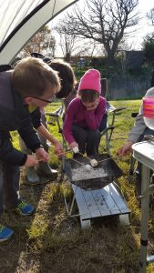 Photo of kids toasting marshmallows.